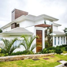 The all-white #exterior of this #magnificent #home is complemented and completed by the solid #wooden #door, while the #mirror #finish of the #large #window allows for a brighter #illumination of the outdoor area. #Design by Roma Arquitetura. Find more #heavenly #architecture with a #tropical touch on #homify  #house #dwelling #modernliving #modernarchitecture #glass #timber