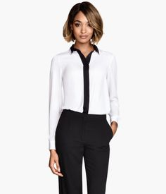 Long-sleeved, straight-cut blouse in woven fabric. Concealed buttons at front and a rounded hem. Slightly longer at back.