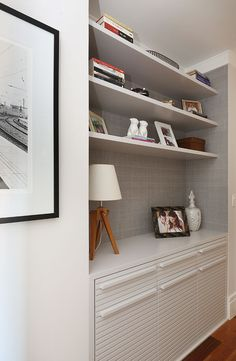 Decoração de apartamento integrado e com crianças. No corredor estante branca com fotos e adornos.