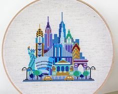 This cross stitch pattern of a stylized London cityscape features Tower Bridge, Big Ben, St Pauls Cathedral, Buckingham Palace, the London Eye, the