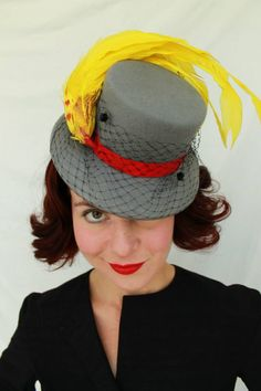 Vintage 1940s-style tilt topper hat in grey felt with a short vintage veil gathered around the front of the hat. A vibrant yellow vintage faux bird with red detailing completes the piece.