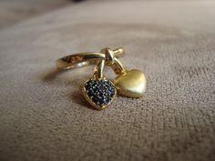Anel em metal dourado com pingentes de coração, tendo um deles aplicação de strass Swarovski preto.  Aro 15 (diâmetro 1,7cm) R$36,00