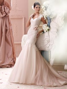 David Tutera for Mon Cheri - 115236 – Meadow -     Light pink wedding dress with corded lace appliqué, tulle and organza over satin trumpet skirt. Lace cap sleeves, tulle and lace appliqué deep Queen Anne neckline, sweetheart corded lace appliquéd bodice features detachable beaded lace belt adorned with three-dimensional organza and lace flowers with beaded centers at natural waist, elaborate open keyhole back bodice finished with cascading covered button closures, exaggerated dropped…