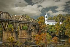 Fall Glory is a photograph I took of the Bibb Graves Bridge where it crosses the Coosa River and leads to the beautiful First Presbyterian Church.  It's location is in Wetumpka, Alabama, nicknamed the City of Natural Beauty.  The rainbow arch bridge was built in 1931 and appeared in several scenes from the movie Big Fish. Photo by Lori Welch Copyright, Lori Welch Photography