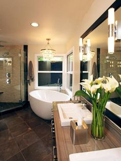 A neutral color palette brings warmth to this transitional bathroom. An elegant chandelier complements the white soaking bathtub, a great spot for relaxing cares away.