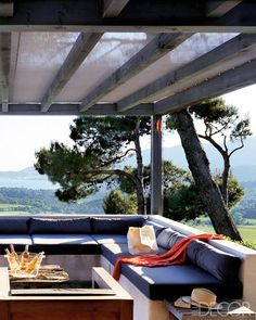 Shaded by a pergola topped with all-weather Batyline fabric, the ipê terrace at a summer home in the South of France was designed by architect Ann Guillec with decorator Florence Watine. The concrete banquette's low back maximizes the view of the Saint-Tropez coastline. The cocktail table is made of reclaimed wood, and the armchair is teak.