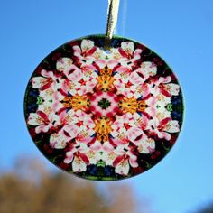 Glass suncatcher adorned with my pink Peruvian lily boho chic mandala new age sacred geometry kaleidoscope design tilted Tickled Pink <br /> <br />This stunning lily glass suncatcher illuminates my geometric mandala kaleidoscope design when light shines through it! It is 3 - ½ inches in diameter and has a beveled edge. The suncatcher comes with a ribbon and ...