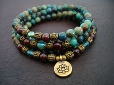womens chrysocolla and garnet mala necklace or wrap bracelet, made from grade aaa+ garnet, chrysocolla, czech crystal, and bronze accents.  choose a charm from left to right:  lotus, om, buddha (top) hamsa, buddha head, ganesha (bottom)   chrysocolla is known as a stone of harmony. it has been used to dispel negativity, and works in a gentle, harmonious way. it is believed to ease fear, anxiety, and guilt, and has been used for protection during pregnancy and childbirth. physically, it is…
