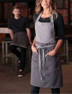 The Soho bib apron. The perfect combination of edgy fashion and forward-thinking functionality. Featuring a contrast color block, buttoned neck strap, reinforced stress points and two patch pockets. Perfect for any kitchen, cafe or rest Cafe Uniform, Waiter Uniform, Restaurant Uniforms, Restaurant Aprons, Work Uniforms, Bib Apron, Apron Dress, Sewing Aprons, Apron Designs