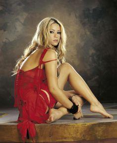 Shakira - sitting beautiful woman in the dark red dress.