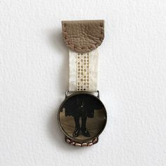 mixed media brooch by Kaija Rantakari - paperiaarre.com - (vintage wrist watch case, vintage photo, vintage lace, recycled leather, freshwater pearls, brooch pin, thread, glue)   diameter of the watch case is 3,1cm / 1.2″ – length 8cm / 3.1″