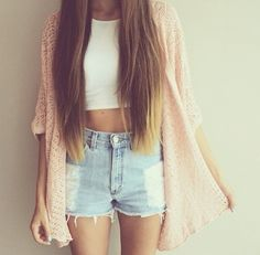 Light pink sweater over a crop top and high waisted shorts.