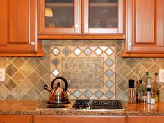 This kitchen's light green tumbled marble backsplash features diamond pattern stainless steel accent tiles that dazzle and shine. The diamond motif is continued with the kitchen hardware. Design by Helen Richardson of Ammie Kim Interior Design