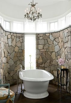 Designed by Karen O'Brian  -KOB Interior Design.. I love it!  I love how the bathroom is part rustic with the fieldstone covering the curved wall and the brown stone tiles, but then you have that gorgeous vintage tub and fabulous chandelier!