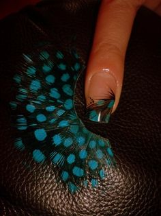 Put a feather on your nail then clear coat over it.  Love it!!