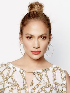 "How to (Easily!) Get the Hottest Hairstyles of Summer - JENNIFER LOPEZ'S TOP KNOT | A perfectly perky top knot needs to start with a ponytail – but resist twisting it and turning it into a bun. ""That's what you would naturally do, but you actually need to tie your hair into a knot,"""