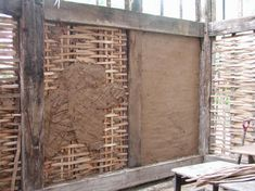 "This is an example of what ""wattle and daub"" walls look like. Wattle and Daub is a way of forming a structure that serves the same purpose as walls today. Wattle was made by weaving reeds together like a basket between two supports (what we would know as studs). Daub created the semi-smooth finish as seen, daub was essentially mud. The Daub would act somewhat like sheetrock or plaster. (my words)"