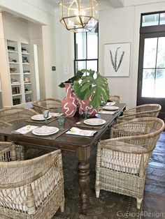 beautiful coastal dining room with dark wood floors and lots of whicker accents and furnishings