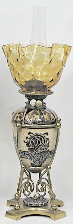 A Doulton Lambeth Oil Lamp. The font of this beautiful oil lamp is done by Florence Barlow and the base is by M. Marshall. The background in the body of the lamp is a crosshatch design in cream shading to brown. The blue design depicts a dragon with mouth open, surrounded by a stylized floral design, the font is housed in a brass frame with brass burner. The amber glass shade features a ruffled edge and thumbprint pattern. England, circa 1801-1900