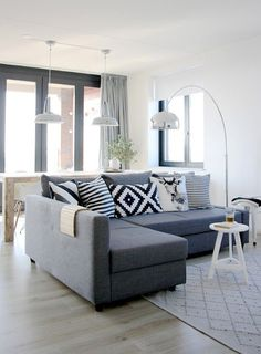 Arco by Achille Castiglioni is the living room highlight in this spacious, contemporary interior featuring a gray sofa, light hardwood floors and clear glass doors.