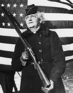 "Mrs. Paul Titus, 77-year-old air raid spotter of Bucks County, Pa., carries a gun as she patrols her beat, Dec. 20, 1941. Mrs. Titus signed-up the day after the Pearl Harbor attack. ""I can carry a gun any time they want me to,"" she declared."