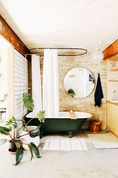 Bathroom Furniture : Beige brick wall, green bathtub, white shower curtain, white tile wall, grey floors, white and beige bath rugs, and beige cabinets -Read More –