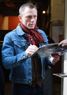 Daniel Craig signing autographs jean jacket red scarf brown sweater grey hair. scarf by Drake's of London