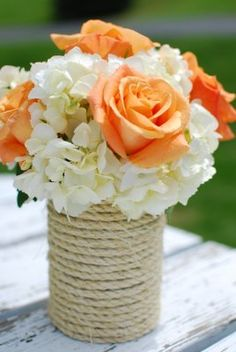 DIY vase wrapped in twine to hold brides flowers at head table!