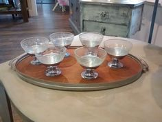 Vintage etched glass sherbet dishes that sit in footed silver stands on a mid century tray with wooden insert.