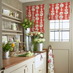 Wooden shelves above a sink are ideal for storing vases in this utility room, while fitted cupboards keep pots and pans neatly hidden away. Vibrant blinds add a pop of colour.