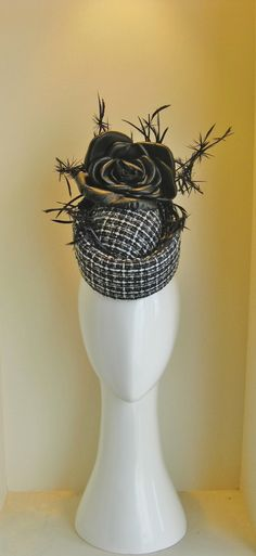 Tribute to the Chanel suit. 2 piece porkpie with black leather rose and feather barbed wire.