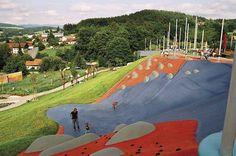 The Big hill slide. Waldkirchen, Baviera. El equipo de arquitectos paisajistas de Rehwaldt Landschaftsarchitekten estilizó una parte del paisaje de este parque, un plano inclinado con cimas, surcos y cantos rodados. El espíritu del proyecto era experimentar con la conexión entre topografía, juego y equipamiento. La cresta y la pendiente son de hormigón proyectado y la mayor parte del recubrimiento es de material sintético. Es un ejemplo de aprovechamiento del terreno como elemento lúdico…