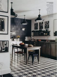 In a classic black and white kitchen, an antique French #cementtile floor.