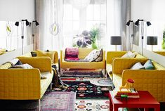 Vardagsrum med fem IKEA soffor i en U-form. Mattor, speglar, lampor och bord.