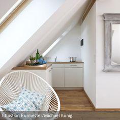 Die Massgefertigte Mini-Küche unter einem Dachflächenfenster dieser Ferienwohnung beherbergt Geschirrspüler, Kühlschrank, Ceran-Kochfeld, sowie Stauraum …