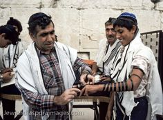 13 yr Jewish boy & his father wrapping the boy's left arm in phylacteries as part of his Bar Mitzvah ceremony at the base of the Western Wall, (Kotel/Wailing Wall)Jerusalem, Israel. The boy wears kippa, phylacteries (tefillin), and prayer shawl (tallit) Observant Jews read from Torah scrolls as part of morning or afternoon services, and boys and girls participate in the reading for their Bar Mitzvah. as in the Torah, Numbers 6, you shall bind these as a sign on your hand, frontlets to your…