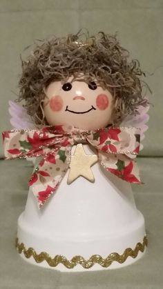 Claire is a Christmas Angel Shelf Sitter hand-crafted from a 4- inch terracotta clay pot and a 3-inch wooden doll head. She has a poinsettia