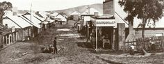 This is Clarke St., Hill End, looking south-west from near the present Royal Hotel, as it appeared in the spring of 1872, when the town was at its heyday. Points of interest are: Merlin's assistant with spare darkslide; the signwriter at work on the signboard outside Manson's new store; the boggy patches in the streets showing the sites of old shafts; the premises of the Australian joint Stock Bank (the two-storey building at far end), with Beyer's cottage just to this side of it.