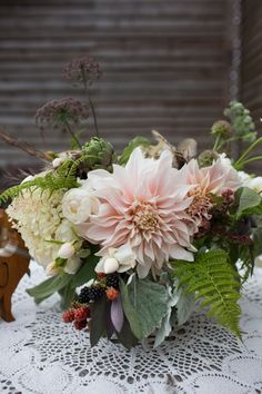 Dahlia and fern woodland table arrangement - photo by www.sarahfalugo.com= What about CAL dahlias (antique blush/peach). pretty here with ferns, dusty and black berries