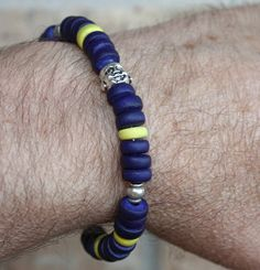Buddha bracelet made with blue and yellow wood rondelle beads with silver Buddha on 22g wire. www.rick724.com