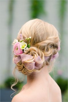 Wedding hair with flowers and ribbons. A sophisticated and romantic updo for a romantic bride.
