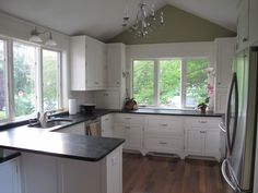 Gorgeous DIY (!) kitchen with white painted cabinets, soapstone countertops, undermount sink, teak floors, lots of windows