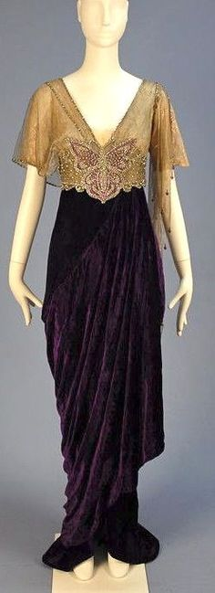 TRAINED VELVET BELLE EPOCH GOWN with JEWELED BODICE 1913. Lush royal purple panne silk having silk lace V-neck bodice asymmetrically draped in gold metallic mesh, high jeweled midriff band with center clear and magenta paste butterfly, hobble skirt layered over short train. Mais