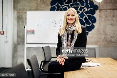 A blonde mature businesswoman wearing a scarf is sitting on a conference table in an office room. A white board with notes is seen in the background.