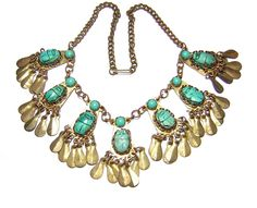 1920s brass Egyptian Revival bib necklace with faience scarabs, along with glass turquoise cabochons. This necklace was likely purchased in Egypt as a souvenir piece. It measures 15 inches and is 1 3/4 in. wide at the front.