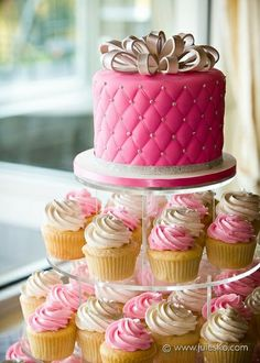 Pink cake on top of a lovely pink and white swirl cupcake tower #wedding #cupcake