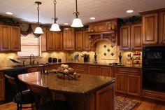 Dark kitchen design with wood cabinets, dark counter tops, wood floor, dark appliances and earth-tone tile back-splash