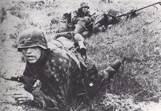Un SS Totenkopf rampe vers sa position de combat sous l'œil attentif de ses collègues.