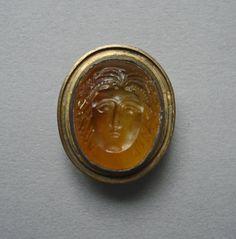 Intaglio; sard; pale, lenticular; head of Medusa to front; in gilt mount.