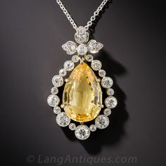 Edwardian Precious Topaz and Diamond Pendant.  Consolidated sunshine glistens and glows from this gorgeous 7.00 carat precious topaz, swinging to and fro inside a sparkling white diamond frame. The golden pear shaped gemstone displays just a tint of apricot overtone. A truly elegant and enchanting, original Edwardian-era jewel, expertly hand-crafted in platinum over 18K gold - circa 1915. The drop measures 1 1/8 inch and suspends from a 17 inch platinum chain.